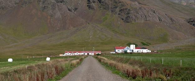 Curral na base de um pasto de montanha, estrada de cascalho com pastagens e cerca de arame