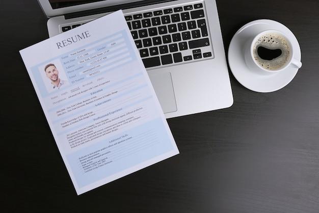 Currículo e laptop na mesa de madeira
