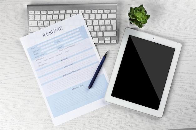 Currículo, tablet e teclado na mesa de madeira