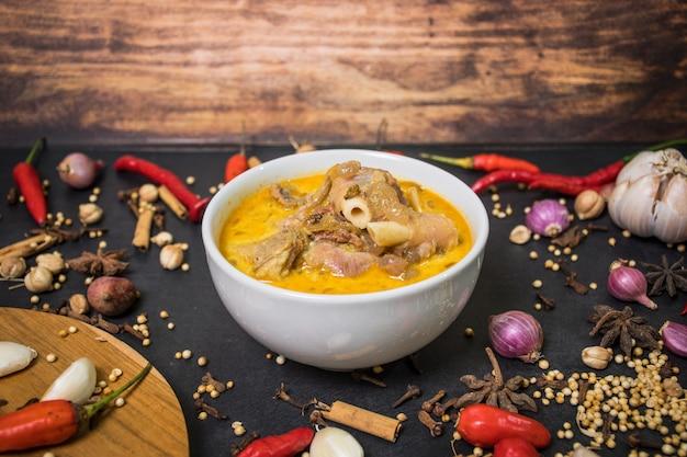 Curry de carneiro com molhos vermelhos na tigela e especiarias um dos menus aqiqah