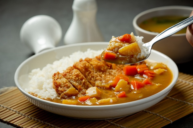 Curry de costeleta de porco frito com arroz na superfície escura