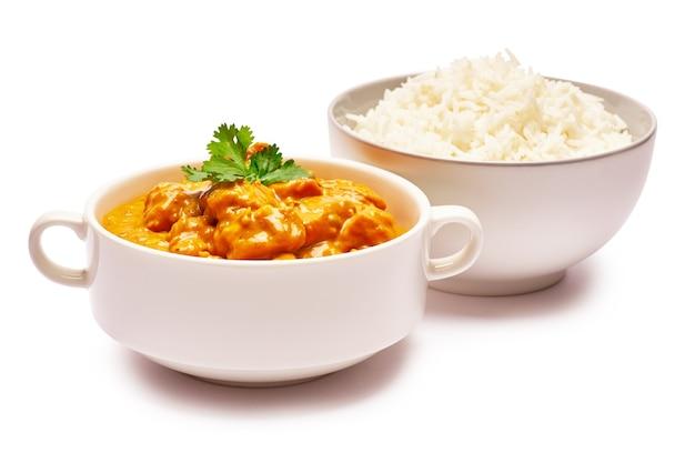 Curry de frango tradicional e uma tigela de arroz cozido isolado