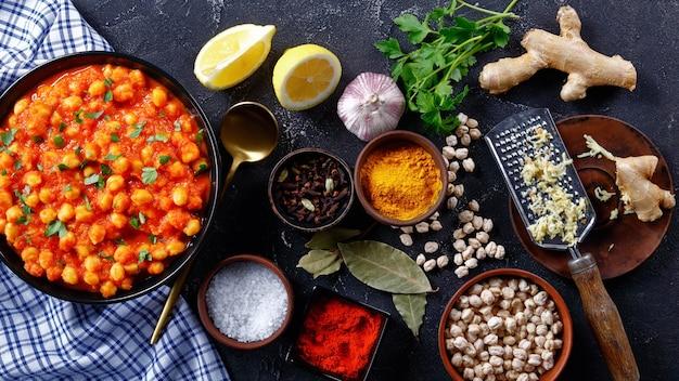Curry picante de grão de bico com ingredientes em um fundo escuro de concreto: