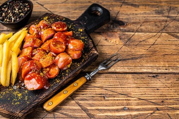 Curry wurst salsichas com batatas fritas em uma placa de madeira. fundo de madeira. vista do topo. copie o espaço.