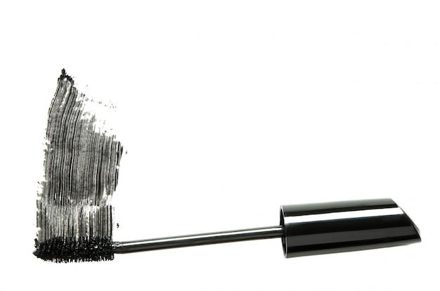 Curso de rímel preto com close-up pincel aplicador isolado no branco