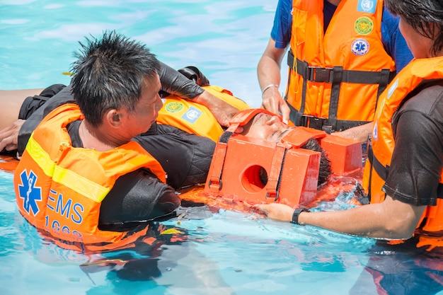 Curso de treinamento de resgate de água vítima acidente de coluna c na piscina