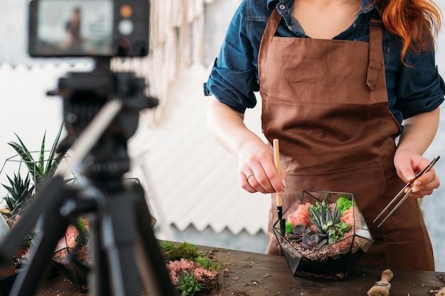 Curso de vídeo diy florarium. mulher mostrando na câmera do smartphone como criar um arranjo floral moderno com suculentas.