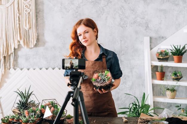Curso de vídeo diy florarium. mulher mostrando na câmera do smartphone como criar um moderno arranjo floral para interior.