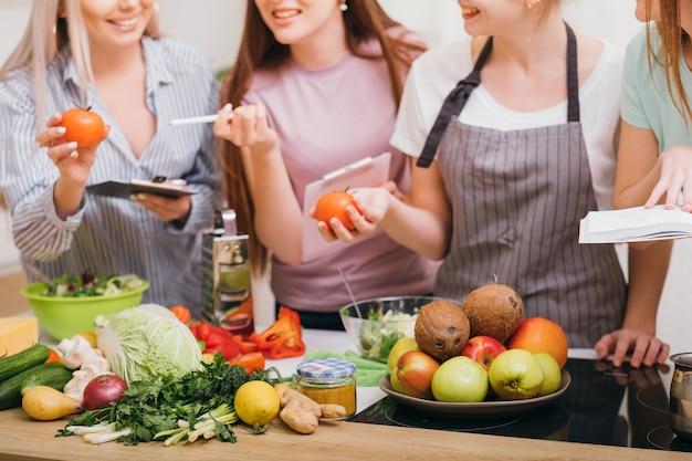 Cursos de culinária. comunicação e educação alimentar. mulheres escolhendo vegetais orgânicos e aprendendo receitas de dieta saudável.