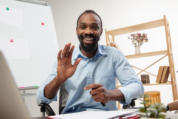 Cursos de inglês online em casa. feche as mãos do homem durante o ensino de alunos remotamente no interior