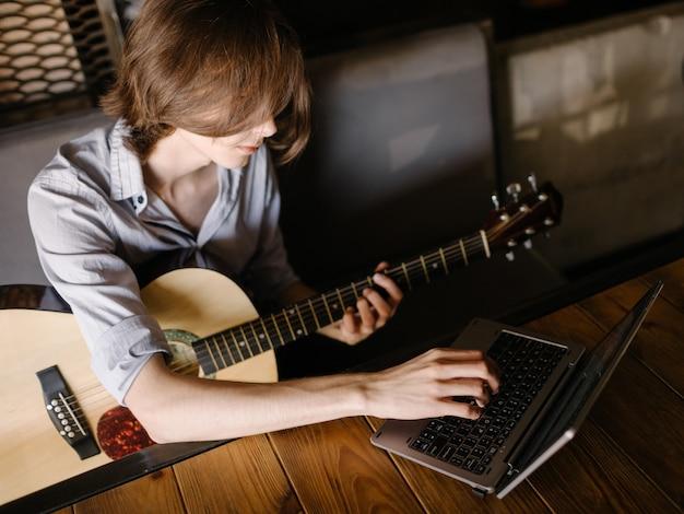 Cursos de música online. jovem aprende a tocar violão através do