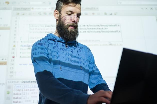 Cursos de programador no centro de educação homem olhando no laptop sua apresentação em segundo plano