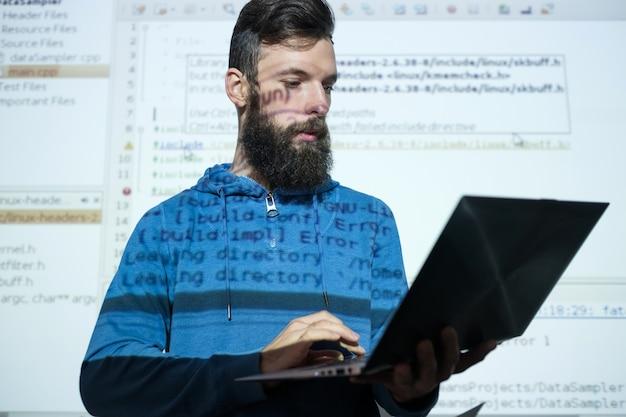 Cursos de programador no centro de educação homem segurando um laptop enquanto dá uma palestra