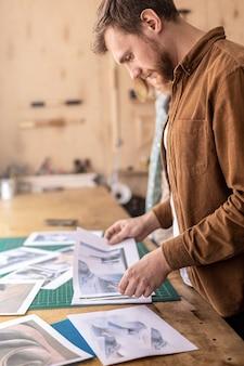 Curtidor profissional masculino procurando fotos, fotos de papel, exemplos de trabalhos manuais em couro