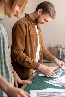 Curtidor profissional masculino procurando fotos, fotos, papel, trabalhos, exemplos de artesanato em couro feito à mão