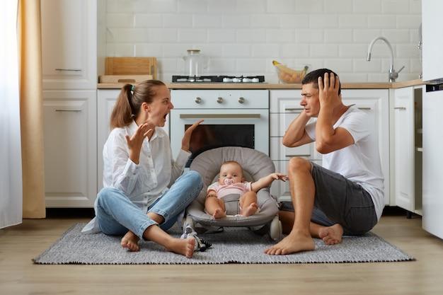 Curto interior discutindo casal sentado no chão da cozinha, esposa gritando alto, marido cobrindo as orelhas com as palmas das mãos, família posando com bebê infantil na cadeira de balanço.