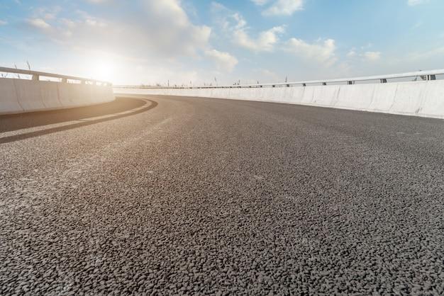 Curva da estrada de asfalto e céu azul e nuvens brancas