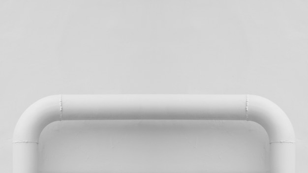 Curva da tubulação de aço branca na parede do cimento branco.