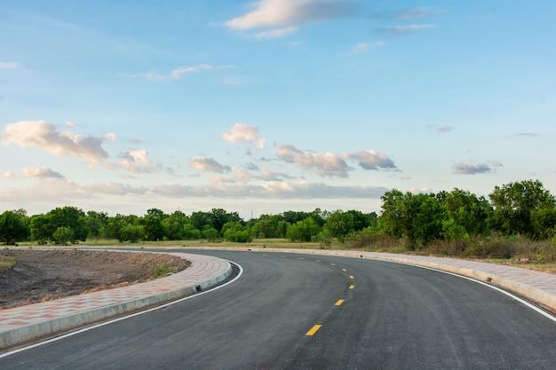 Curva de estrada de asfalto vazia e céu azul limpo no fundo de dia de verão com espaço de cópia