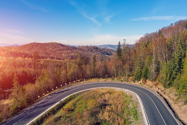 Curva difícil em uma estrada sinuosa nas montanhas de outono vista de drone