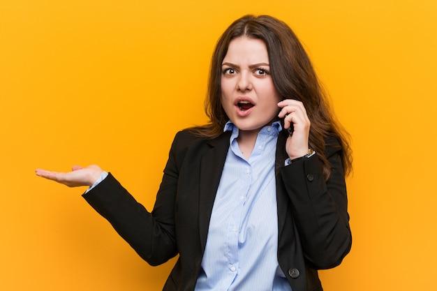 Curvado novo mais a mulher de negócio do tamanho que guarda um telefone impresso guardando o copyspace na palma.