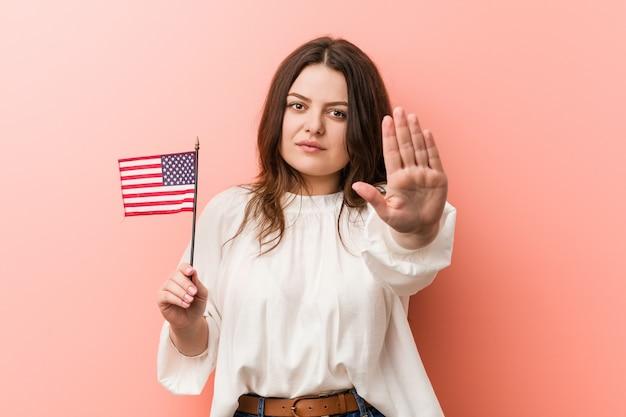Curvado novo mais a mulher do tamanho que guarda uma bandeira de estados unidos que está com a mão estendido que mostra o sinal da parada, impedindo-o.