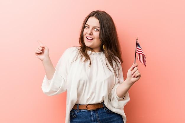 Curvado novo mais a mulher do tamanho que guarda uma bandeira de estados unidos que sorri alegremente apontando com dedo indicador afastado.