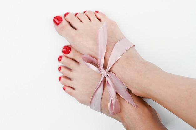 Curvar-se nas pernas femininas. em um espaço isolado. presente de pele limpa dos pés.