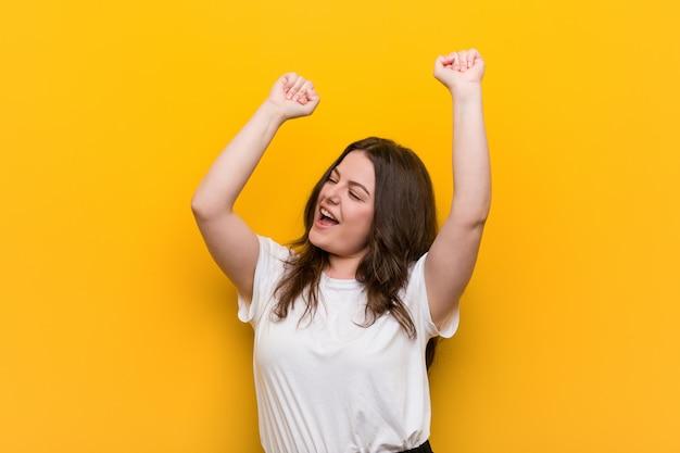 Curvilínea jovem plus tamanho mulher comemorando um dia especial, saltos e levantando os braços com energia.