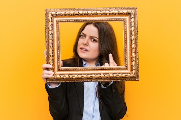 Curvilínea jovem plus tamanho mulher de negócios, segurando um quadro apontando com o dedo para você, como se convidando se aproximar.