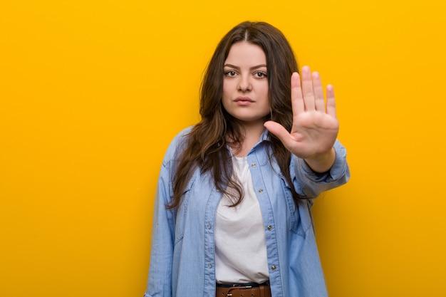 Curvilínea jovem plus tamanho mulher em pé com a mão estendida, mostrando o sinal de stop, impedindo-o.
