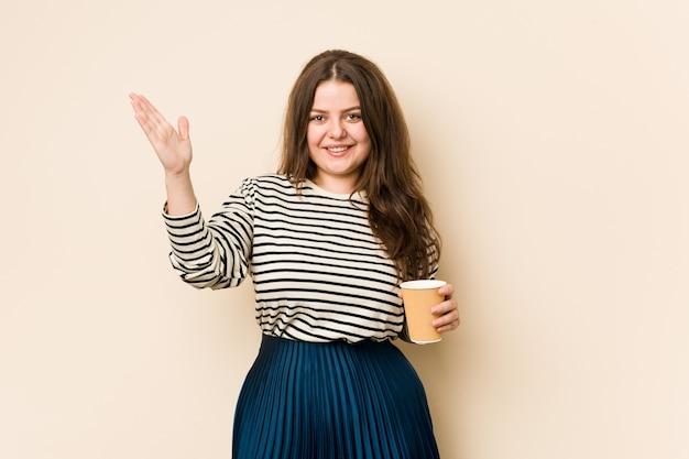 Curvilínea jovem segurando um café, recebendo uma agradável surpresa, animada e levantando as mãos.