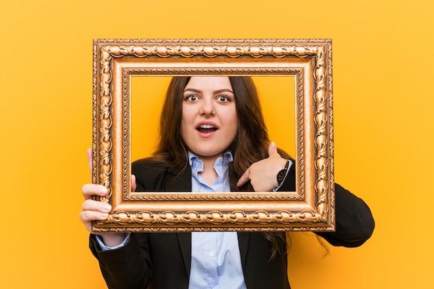 Curvilínea mais jovem mulher de negócios de tamanho, segurando um quadro surpreendeu apontando para si mesmo, sorrindo amplamente.