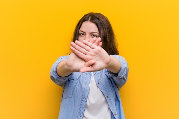 Curvilínea mais jovem tamanho mulher fazendo um gesto de negação