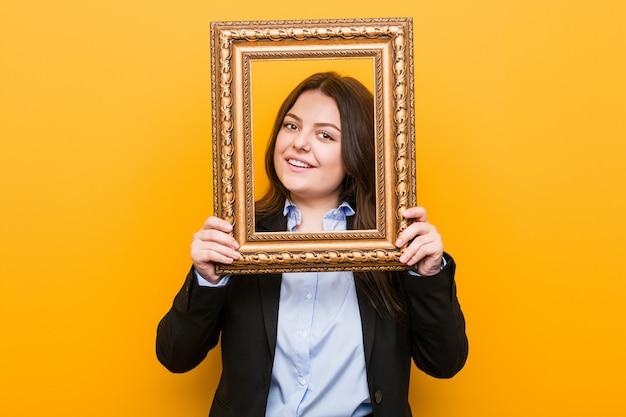 Curvilínea mais jovem tamanho mulher segurando um quadro feliz, sorridente e alegre.