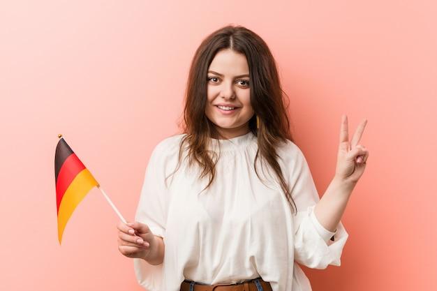 Curvilínea mais jovem tamanho mulher segurando uma bandeira da alemanha mostrando o número dois com os dedos.