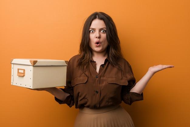 Curvilínea mais jovem tamanho mulher segurando uma caixa impressionado segurando na palma da mão.
