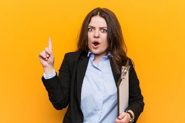 Curvilínea nova mais a mulher de negócio do tamanho que guarda uma prancheta que tem alguma grande ideia, conceito da faculdade criadora.