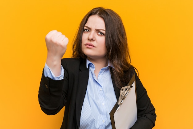 Curvilíneas novas, mais tamanho mulher de negócios holdingclipboard mostrando o punho, expressão facial agressiva.