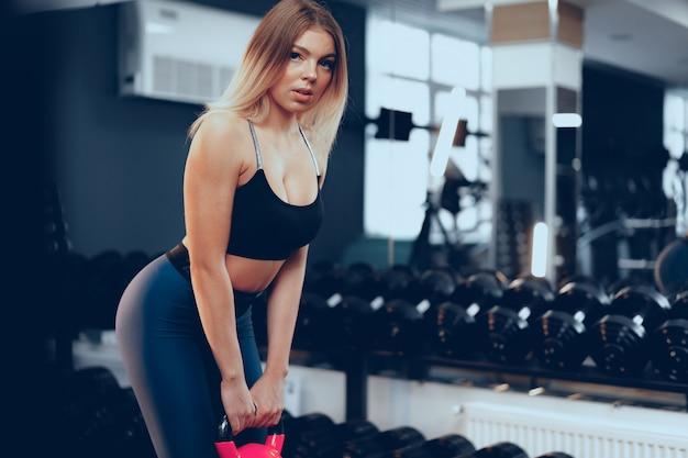 Curvy jovem loira em forma de roupa esportiva levantando halteres em uma academia