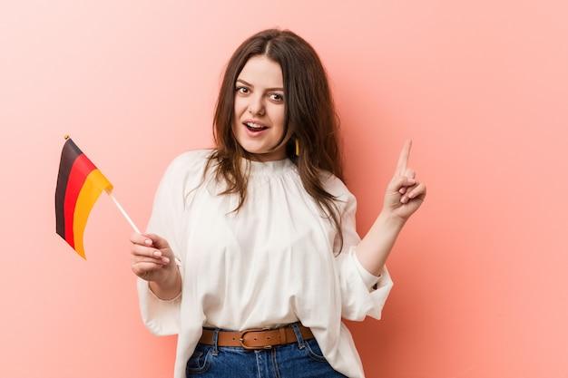Curvy novo mais a mulher do tamanho que guarda uma bandeira de alemanha que sorri alegremente apontando com dedo indicador afastado.
