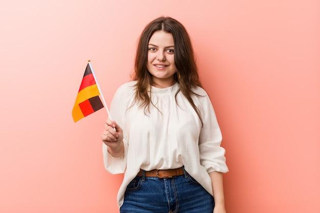 Curvy novo mais a mulher do tamanho que mantém uma bandeira de alemanha feliz, sorrindo e alegre.