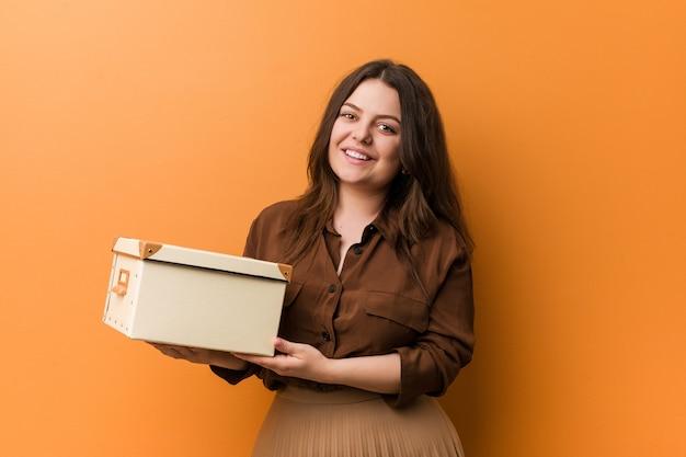 Curvy novo mais a mulher do tamanho que mantém uma caixa feliz, sorrindo e alegre.