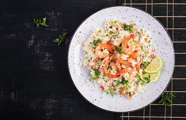 Cuscuz com camarão assado, tomate, cebola roxa, amêndoa e salsa. comida marroquina com cuscuz e camarão. vista superior, configuração plana