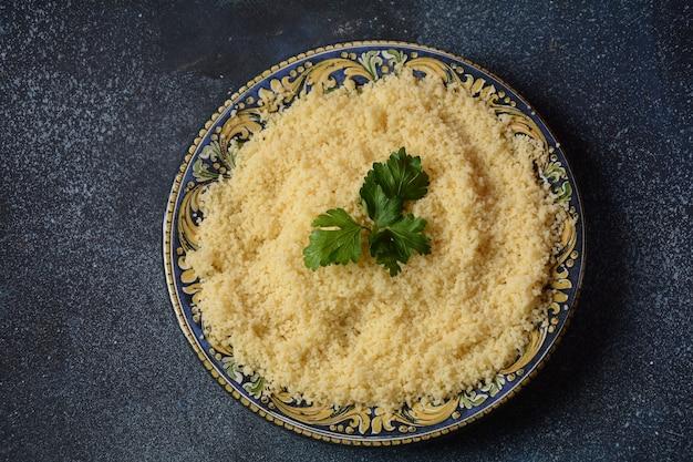 Cuscuz cozido com salsa verde em prato de cerâmica