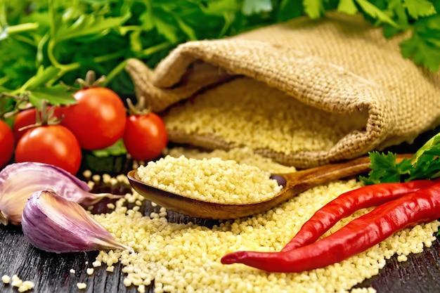 Cuscuz cru em uma colher e um saco de estopa, tomate, pimenta, ervas e alho no fundo de uma placa de madeira escura