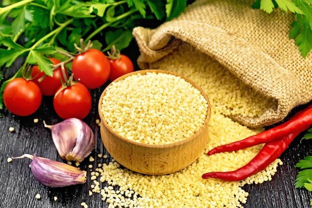 Cuscuz cru em uma tigela e um saco de estopa, tomate, pimenta, ervas e alho no fundo da placa de madeira