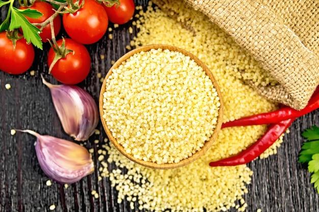 Cuscuz cru em uma tigela e um saco de estopa, tomate, pimenta, ervas e alho no fundo de uma placa de madeira escura vista de cima