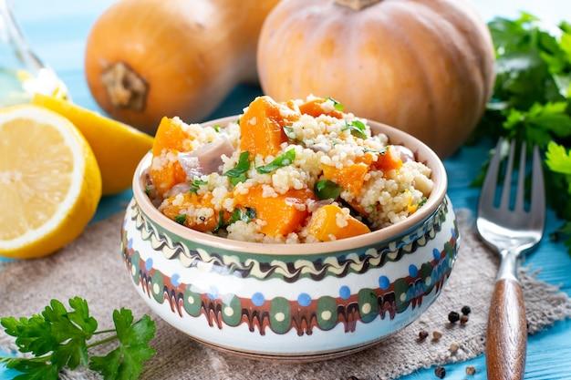 Cuscuz de outono com abóbora e legumes na mesa de madeira