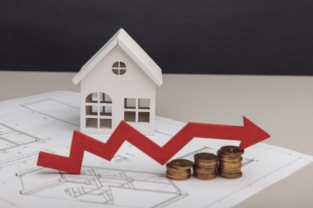 Custo de construção e conceito de investimento casa branca e seta para cima na pilha de moedas com desenho